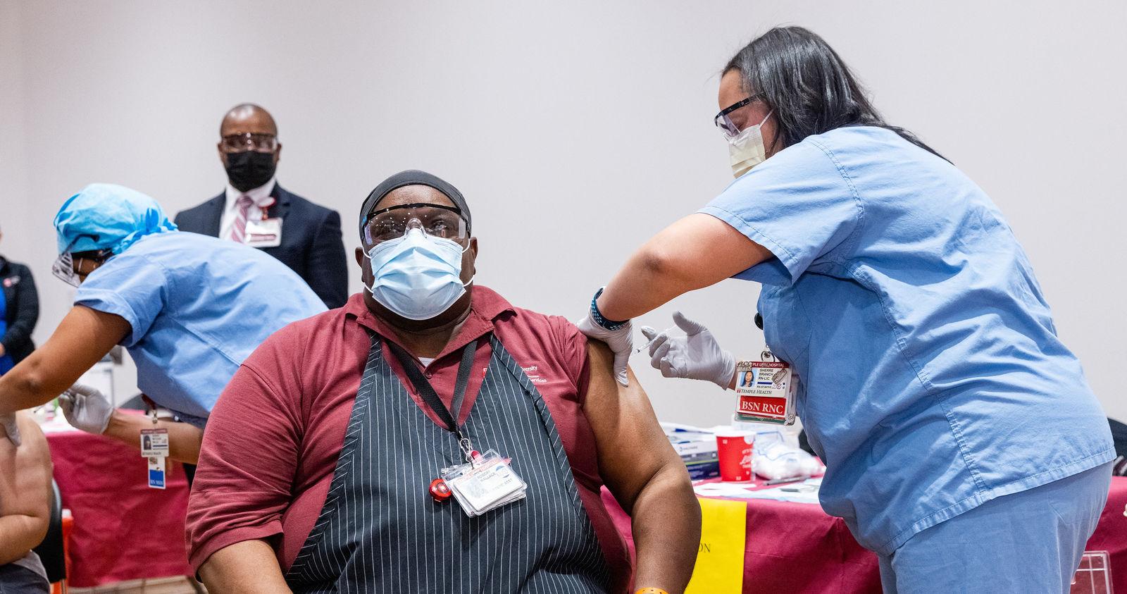 nurse administers covid vaccine
