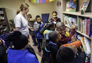 Nursing student helps children choose books at a library
