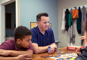 Tim Gallagher plays a board game with his students