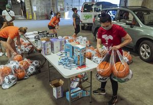 people packing bags of at-home sports equipment