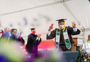 a smiling student makes a peace sign as he crosses the stage at graduation