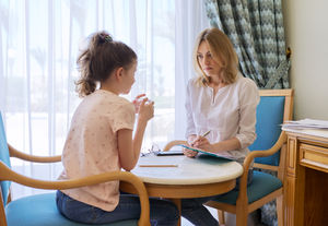 young girl and therapist talk in therapists office