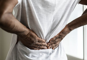 a man pushes against his back, in pain