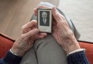 Elderly person holds old photograph of man