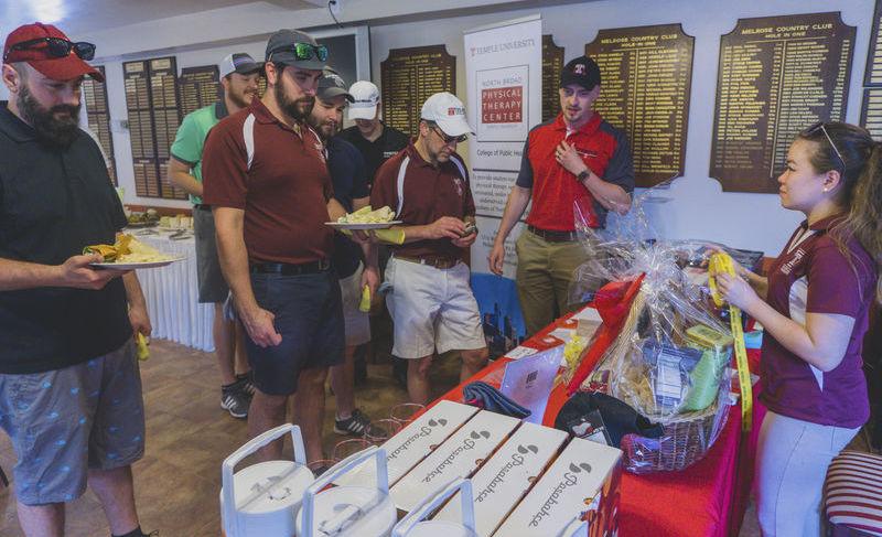 Participants choosing golf clubs