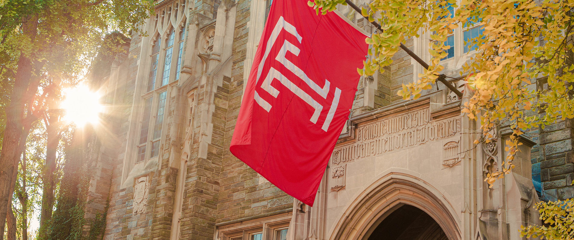 Temple flag hanging on a campus building