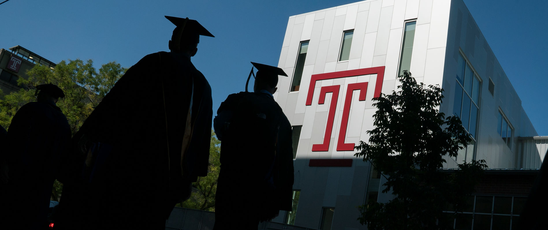 Two students in caps and gowns walking on campus next to building with Temple T on the front