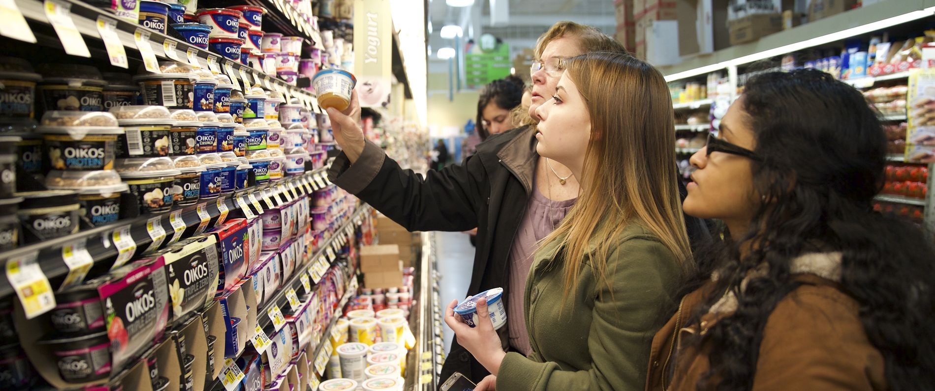 Professor and students examining the nutrition label of a yogurt in the supermarket