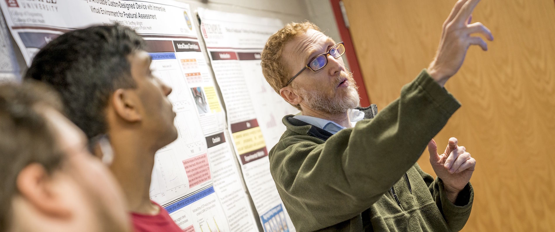 Professor Geoff Wright pointing at a research poster