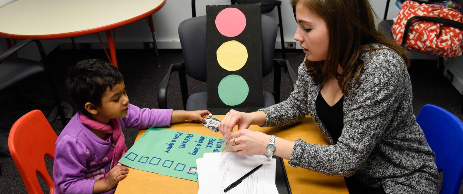 Speech pathologist showing little girl a set of photos