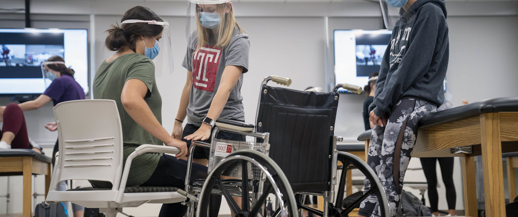 two OT students help one student move from a chair to a wheelchair