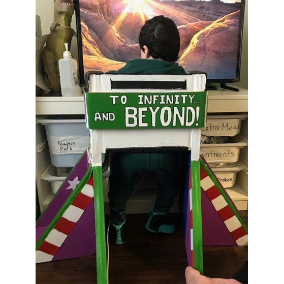 "a child sits in a chair decorated as a rocket ship, with the words ""to infinity and beyond"" written on the chair."
