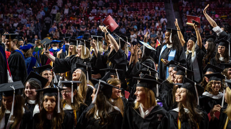 Group of graduates in cap and gown celebrating in the Liacouras Center