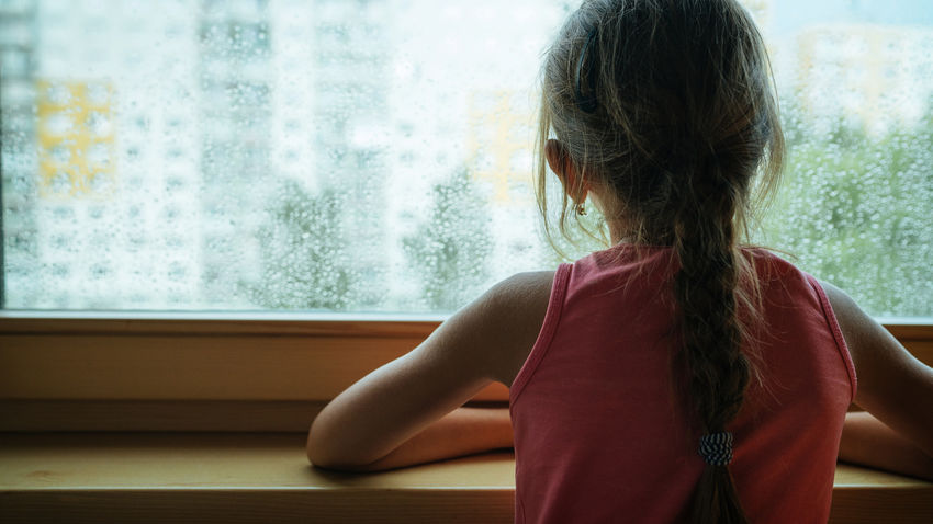 a young girl looks out a rainy window