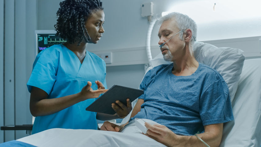 patient and nurse communicating over a tablet
