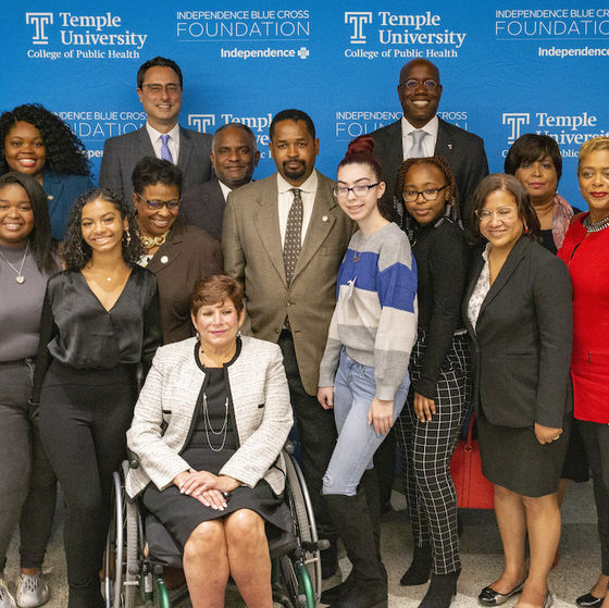 Temple students and administrators, IBC personnel, and government representatives posing for a photo at a press conference