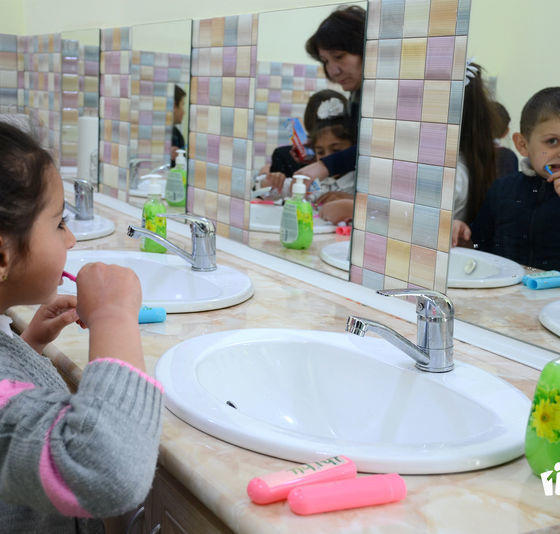 Child using a mirror while brushing teeth