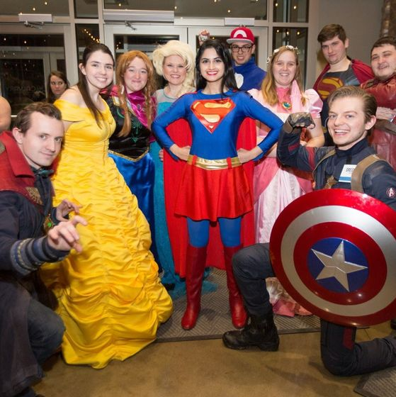 students visiting hospital or school as superheroes