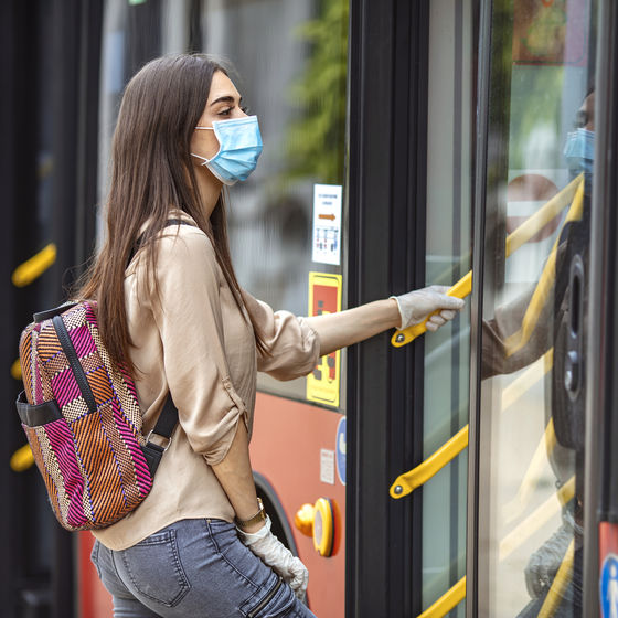a woman wearing a face mask boards a public transit bus