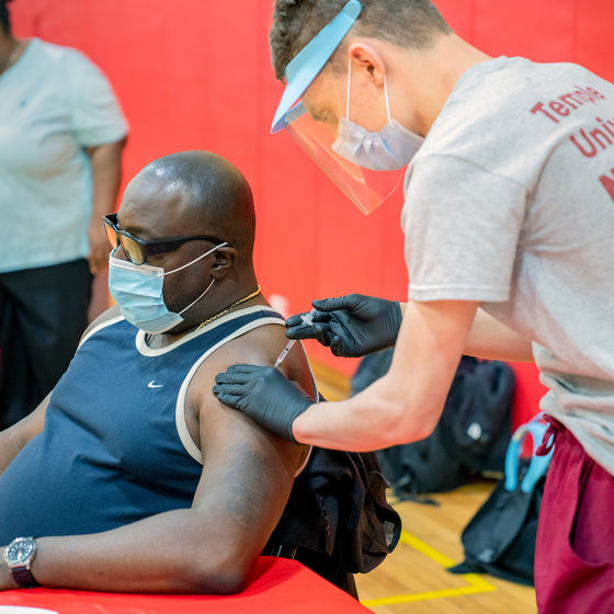 a nursing student administers a covid-19 vaccine into the arm of a seated man in a gymnasium.